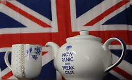 Tea pot and cup with Now Panic and Freak Out written thereon with Union Jack flag in the background